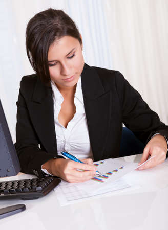 Low angle view of a relaxed smiling beautiful businesswoman sitting behind her desk working at her computer Stock Photo - 16522116