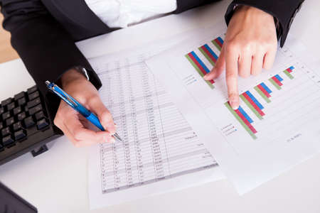 Overhead cropped image of female hands working with bar graphs and a spread sheet as she analyses data Stock Photo - 16522158