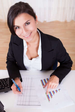 Overhead cropped image of female hands working with bar graphs and a spread sheet as she analyses data Stock Photo - 16522625