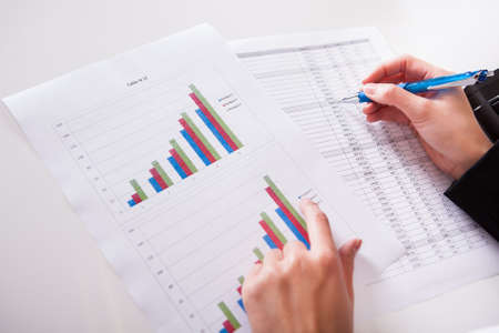 data sheet: Overhead cropped image of female hands working with bar graphs and a spread sheet as she analyses data