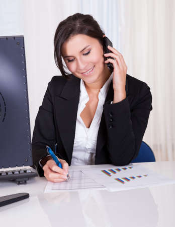 Happy brunette business woman takes notes whilst listening to someone on her mobile phone Stock Photo - 16522290