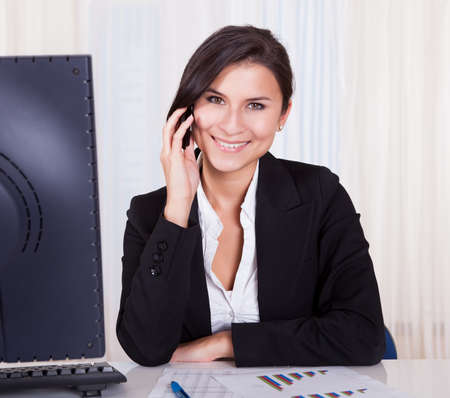 Happy brunette business woman listening to someone on her mobile phone Stock Photo - 16522350