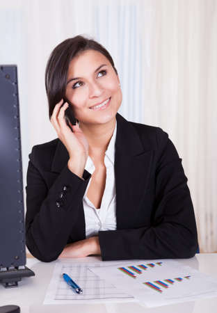 Happy brunette business woman listening to someone on her mobile phone Stock Photo - 16522168