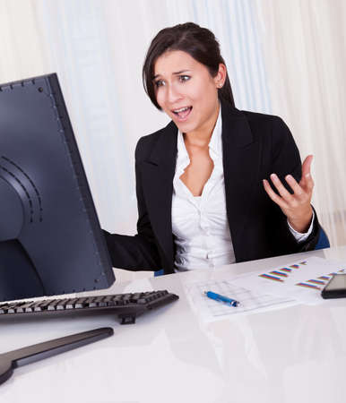 Studio shot of a frustrated businesswoman looking at her computer screen in dismay Stock Photo - 16522594