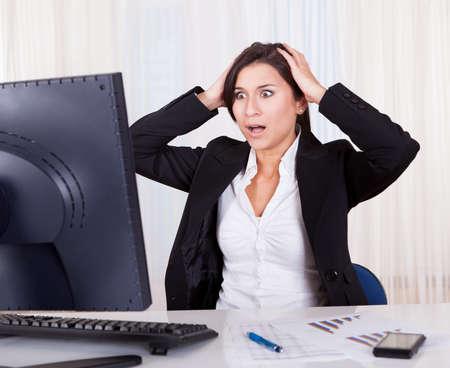 sgomento: Studio shot di una donna d'affari frustrato guardando lo schermo del suo computer in sgomento Archivio Fotografico