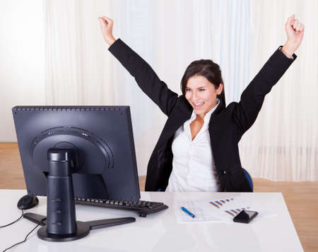 Successful businesswoman celebrating by throwing her arms up on the air as she sits back in her office chair and looks at her computer screen Stock Photo - 16522369