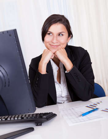 Low angle view of a relaxed smiling beautiful businesswoman sitting behind her desk working at her computer Stock Photo - 16522671