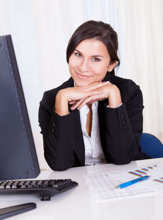 Low angle view of a relaxed smiling beautiful businesswoman sitting behind her desk working at her computer Stock Photo - 16522423