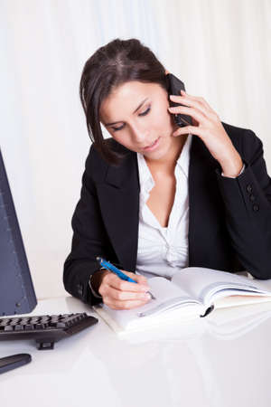 Happy brunette business woman takes notes whilst listening to someone on her mobile phone Stock Photo - 16522531