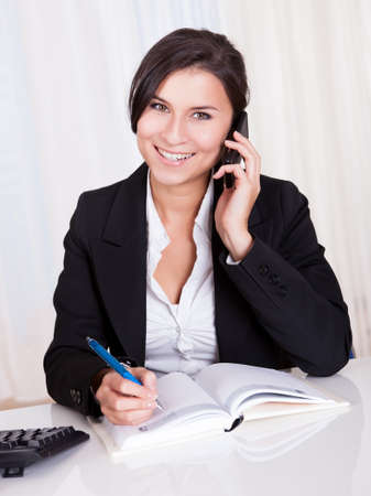 Happy brunette business woman takes notes whilst listening to someone on her mobile phone Stock Photo - 16522313