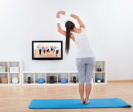 woman working out: Woman practicing yoga at home standing on a mat on her living room floor while watching and participating in a class