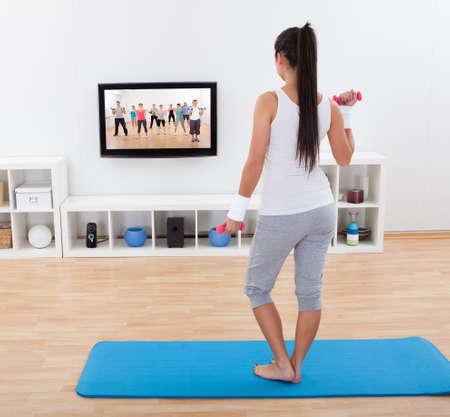 Rear view of a shapely barefoot young woman working out with dumbbells standing on a mat in her living photo