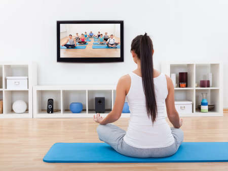 meditation room: Rear view of a spiritual young woman sitting on a mat meditating at home while watching Stock Photo