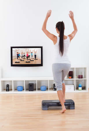 stepping: Rear view of an athletic barefoot young woman doing home exercises while watching program on television