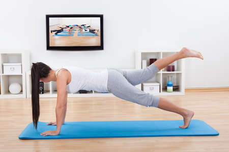physical activity: Woman practicing yoga at home standing on a mat on her living room floor while watching and participating in a class