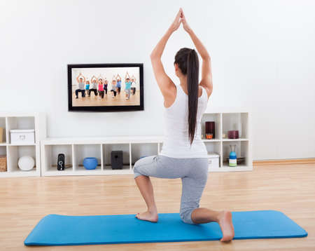 kneeling woman: Rear view of an athletic barefoot young woman doing home exercises while watching program on television