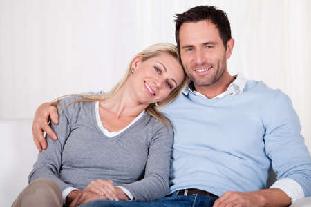 Affectionate couple relaxing on a sofa with the mans arm around his wifes shoulders as she rests her head on his shoulder Stock Photo - 16886343