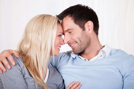 rubbing noses: Romantic young couple expressing their love by rubbing noses as they sit close together on a sofa