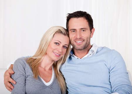 coppia in casa: Coppia affettuoso relax su un divano con il braccio intorno alle spalle mans mogli mentre lei appoggia la testa sulla sua spalla