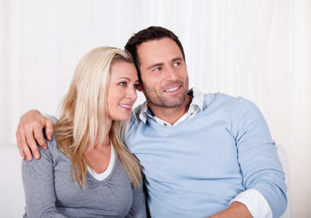 Affectionate couple relaxing on a sofa with the mans arm around his wifes shoulders as she rests her head on his shoulder Stock Photo - 16886331