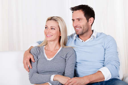 Affectionate couple relaxing on a sofa with the mans arm around his wifes shoulders as she rests her head on his shoulder Stock Photo - 16886335