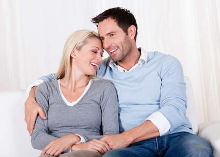 Romantic young couple expressing their love by rubbing noses as they sit close together on a sofa Stock Photo - 16886332