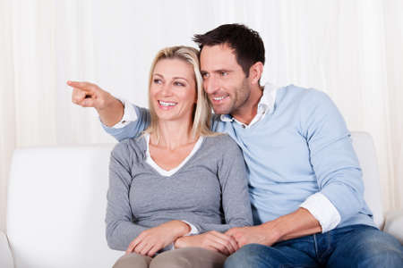 Laughing couple sitting close together on a couch pointing off screen to the left and looking in that direction Stock Photo - 16886347