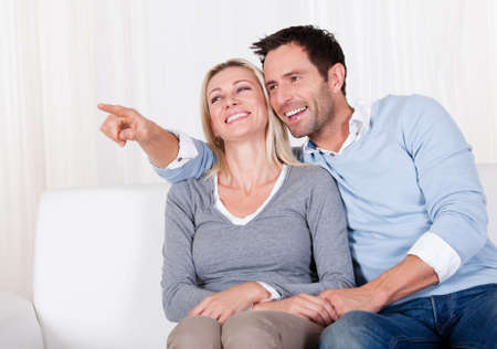 Laughing couple sitting close together on a couch pointing off screen to the left and looking in that direction Stock Photo - 16886342