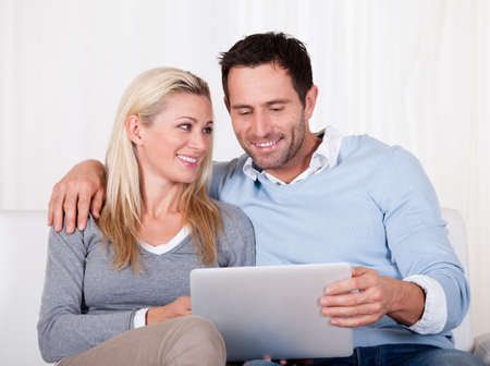 Beautiful young couple with lovely smiles sitting side by side on a sofa looking at a tablet together photo