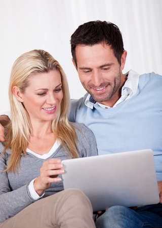 Beautiful young couple with lovely smiles sitting side by side on a sofa looking at a tablet together Stock Photo - 16886330