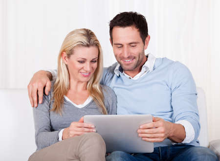 Beautiful young couple with lovely smiles sitting side by side on a sofa looking at a tablet together Stock Photo - 16886336