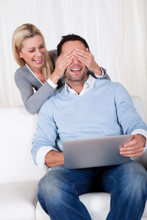Man and woman laughing over information on the screen of a laptop with the man seated on a sofa and the woman leaning over his shoulder Stock Photo - 16886334