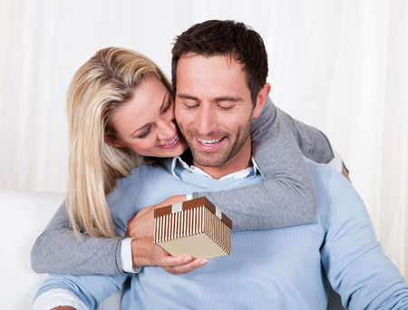 gift giving: Smiling beautiful woman leaning over her husbands shoulder giving him a surprise gift Stock Photo