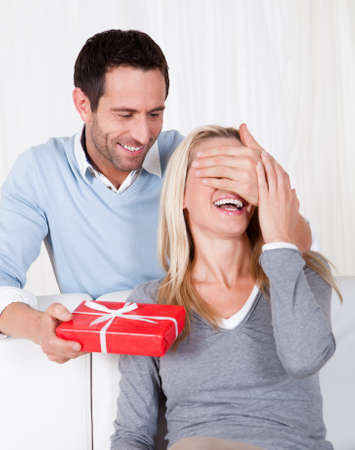 hands covering eyes: Man giving his wife a surprise gift at home