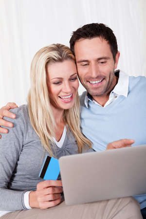 Couple having fun shopping online sitting laughing as they read the screen on their tablet with the woman holding a credit card Stock Photo - 16886428