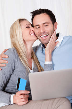 Couple having fun shopping online sitting laughing as they read the screen on their tablet with the woman holding a credit card photo