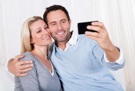 Beautiful smiling young couple photographing themselves on a mobile or smartphone posing close together with his arm around her photo
