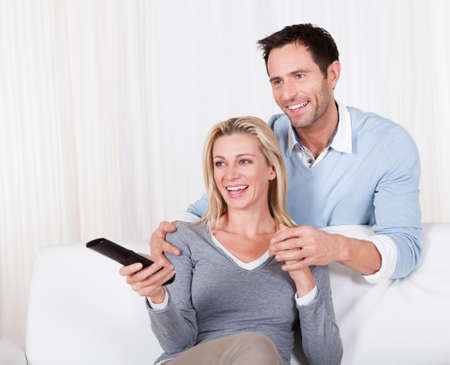 Cheerful couple watching TV sitting at sofa photo