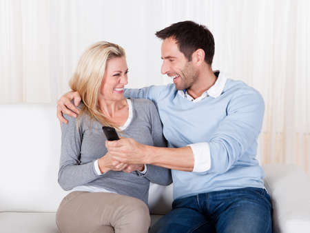 Young couple fighting for TV remote at home photo