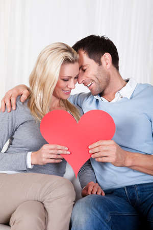 Romantic couple sitting on a sofa in a loving embrace laughing as they hold up a red paper heart for Valentines day photo