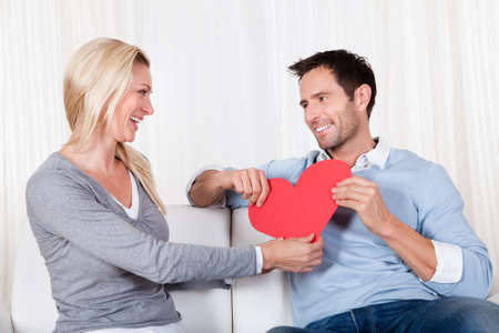 adult valentine: Romantic couple sitting on a sofa in a loving embrace laughing as they hold up a red paper heart for Valentines day Stock Photo