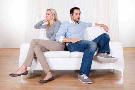 relationship problems: Couple who have fallen out over a disagreement sitting on a sofa Stock Photo