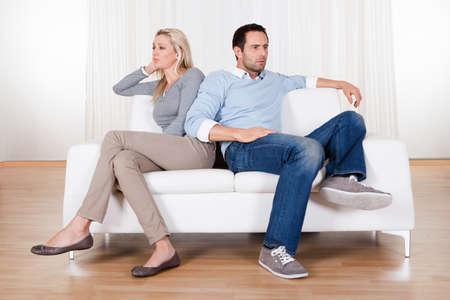 woman issues: Parejas que han ca�do en m�s de un desacuerdo sentado en un sof� Foto de archivo