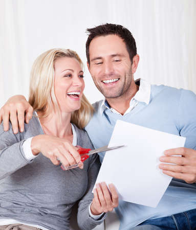 cutting costs: Laughing woman about to cut up a document poised with the scissors at the ready while being watched by her husband Stock Photo
