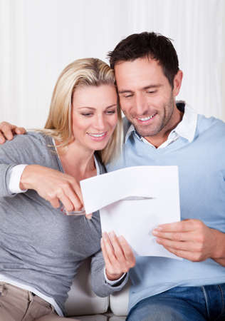 cut up: Laughing woman about to cut up a document poised with the scissors at the ready while being watched by her husband Stock Photo