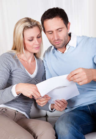 cutting costs: Woman about to cut up a document poised with the scissors at the ready while being watched by her husband Stock Photo