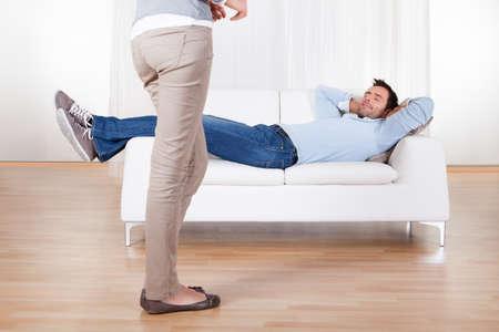 novios enojados: Marido perezoso en el sof� y su esposa