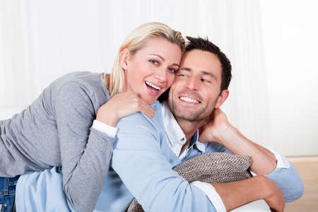 mid adult couple: Happy attractive young man and woman smiling and cuddling as he relaxes on the sofa