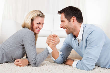 female wrestling: Attractive young man and woman laughing together as they lie on the carpet arm wrestling Stock Photo