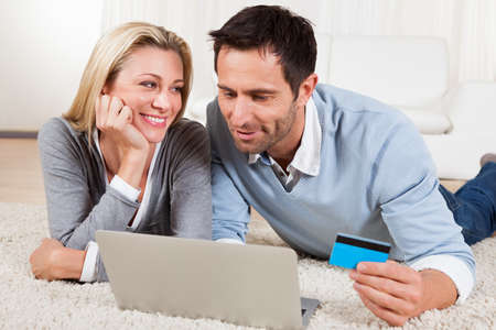 Attractive young couple lying on the floor together looking at the screen of their laptop while shopping online Stock Photo - 16874345